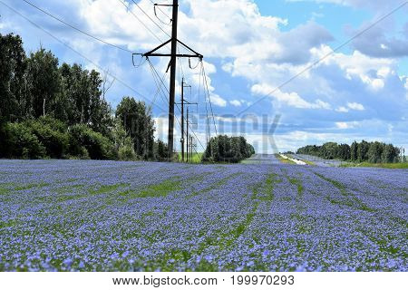 Electrical wires and highway road trail in blue flax colors against a blue sky with clouds