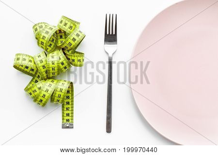 Losing weight. Strict diet. Empty plate and measuring tape on white background top view.