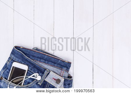 Phone and music earphone in Jean pocket with white copy space