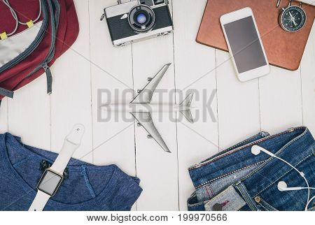 Travel fashion and accessories flat lay on white wood