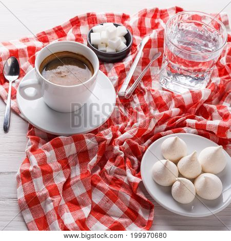 Morning coffee at restaurant. White porcelain cup of black bitter coffee with treats on stylish checkered tablecloth on wooden background, copy space