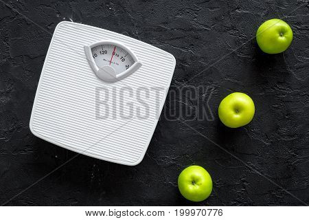 Diet for losing weight. Bathroom scale and apples on black background top view.