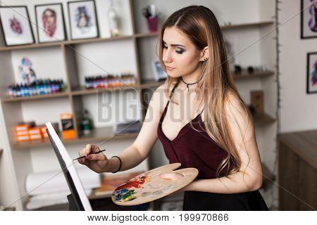 Artist painting in her workshop