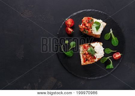 Italian appetizer on black background. Crusty bruschetta with concasse tomatoes, stracciatella cheese decorated with spinach. Delicious and healthy restaurant meals, top view, copy space