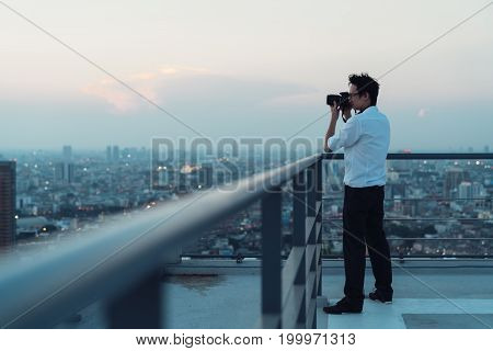 Asian man taking cityscape photo on building rooftop in low light situation.