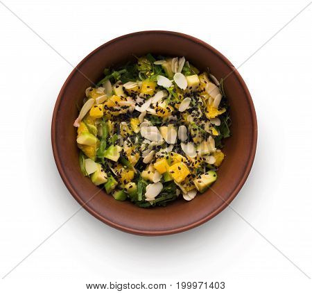 Healthy japanese restaurant food isolated at white. Bowl of avocado and ogange salad with seaweed, almond flakes and black sesame. Asian fusion cuisine, top view