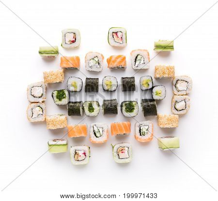 Sushi assortment isolated on white background. Big set of seafood rolls covered with salmon, nori, cucumber and sesame. Japanese food delivery