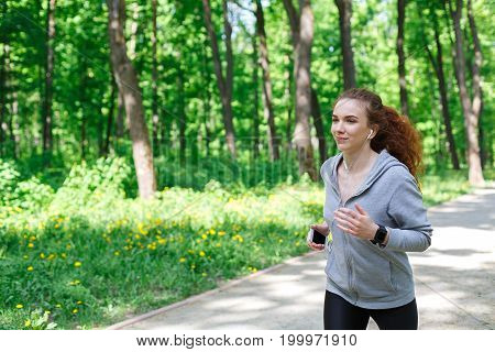 Woman listening music during morning running in park, copy space