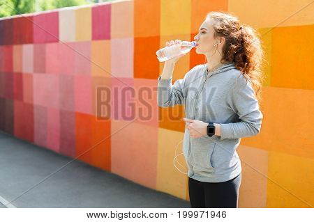 Young woman runner is having break, drinking water while jogging, colorful background