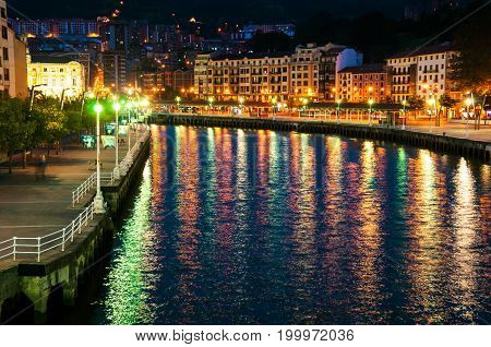 Bilbao, Spain. Aerial view of Bilbao, Spain city downtown with a Nevion River and promenade at night. Reflection in the river