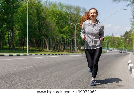 Young sporty woman jogging on road during morning workout, copy space