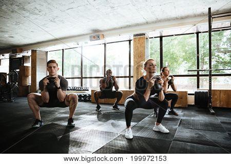 Picture of group of multiethnic sports strong people make sport exercise with weight. Looking aside.