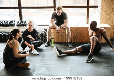 Image of group of sports strong people sitting in gym. Looking aside drinking water.