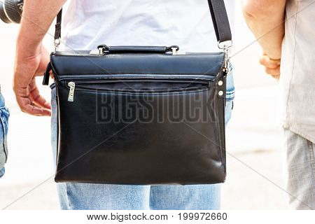 Black briefcase of leather on the shoulder of a man