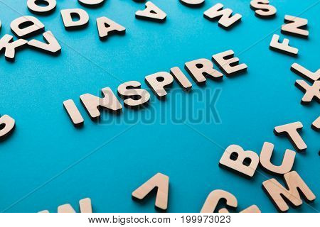 Word Inspire on blue background with pile of wooden letters. Creativity, imagination concept