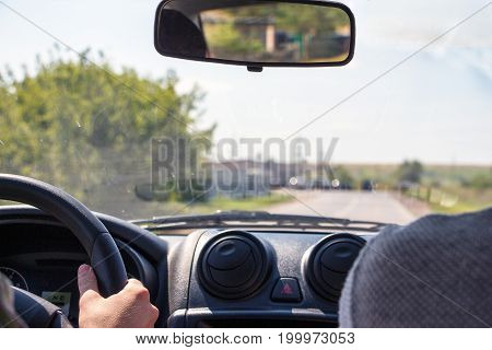 Men hands on the wheel of a car.