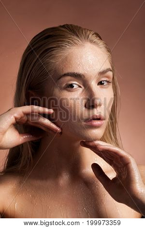 Beautiful sensual woman with wet face and drops of water in studio photo on brown background. Sensuality and spa. Skin care