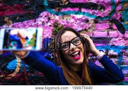 Hipster woman taking selfie photos in colorful abstract background