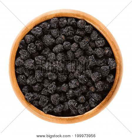 Aronia berries in wooden bowl. Dried ripe black chokeberries, Aronia melanocarpa. The Fruits are used as flavoring or colorant. Isolated macro food photo close up from above on white background.