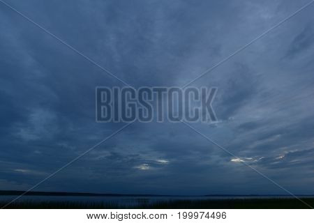 Bad weather cloudy sky dark blue above the lake
