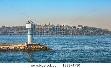 Pier and lighthouse on Bosphorus and sultan palace Topkapi on background in Istanbul Turkey