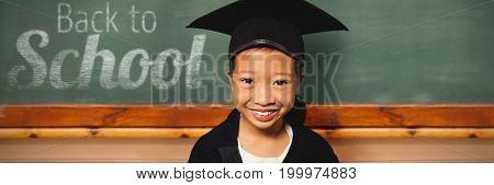 Portrait of smiling girl wearing mortarboard against blackboard