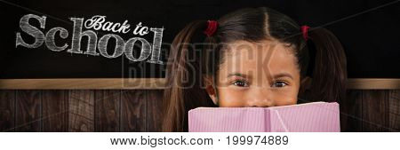 Schoolgirl covering mouth with book against blackboard on wooden wall