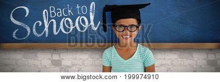 Portrait of cheerful girl wearing eyeglasses and mortarboard against bueboard on wall  in school