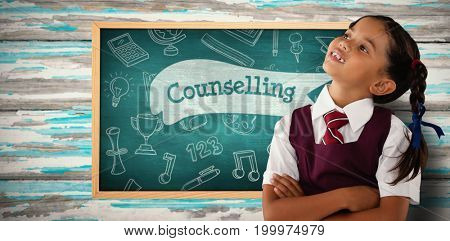 Thoughtful schoolgirl looking away against counselling against green chalkboard