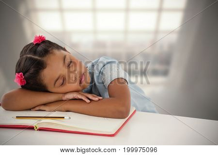 Girl napping on book at desk against room with large window showing city