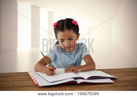 Girl writing in book at desk against digitally generated room