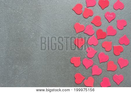 Many red and pink hearts on a grey concrete background.Valentine's day