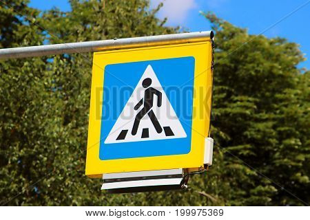 Road sign pedestrian crossing on background of trees