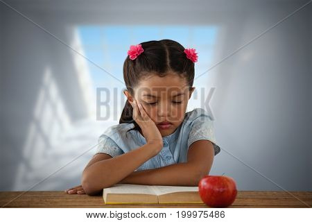 Concentrated girl reading book at desk against room with large windows