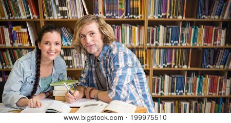 College students doing homework in library against various books on shelf