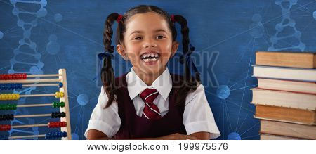 Cheerful schoolgirl with stack of books  against blue background
