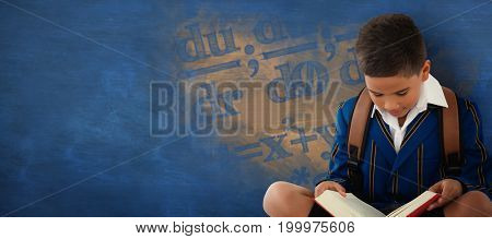 Schoolboy reading book over white background against blue background