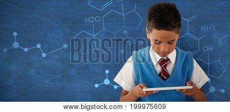Schoolboy using digital tablet against blue background