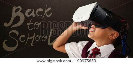 Close-up of schoolgirl using virtual reality headset against blackboard