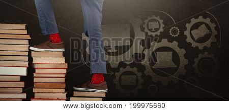 Low section of boy climbing stack of books against blackboard