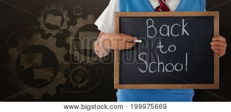 Midsection of schoolboy holding slate with back to school text against blackboard