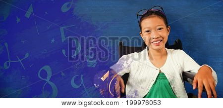 Young girl smiling while sitting on wheelchair against blue background
