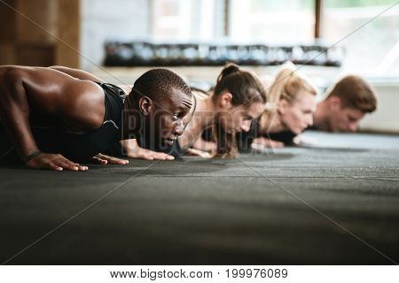 Image of group of multiethnic sports strong people make sport exercises in gym.