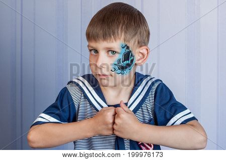 Young boy with Marine themes face painting Sailboat