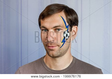 Young man with face painting football fan mask