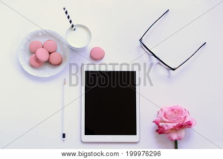 Modern styled desk top with cookies, milk, eyeglasses, rose and tablet in pink and white. Copy space.