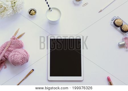 Modern styled desk top with flowers, yarn, tablet, milk, cookies, and beauty products. Copy space.