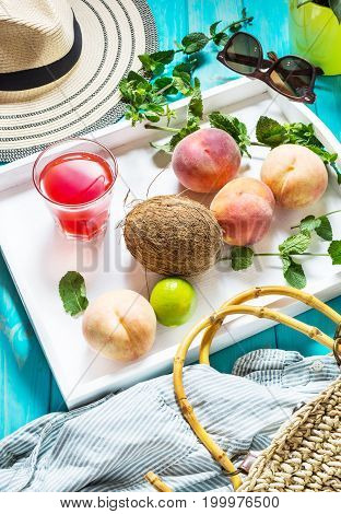 Summer vacation background theme with bag, hat, coconut, sunglasses and Peaches on blue wood background
