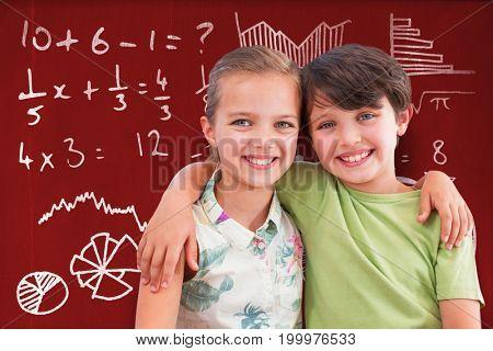 Portrait of happy siblings against blackboard with copy space on wooden board