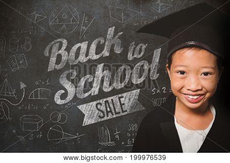 Portrait of smiling girl wearing mortarboard against close-up of blackboard